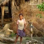 Local girl pumping water, Thakudwara